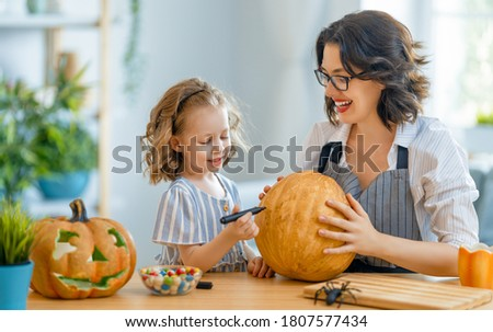 Happy family preparing for Halloween. Mother and child carving pumpkins at home.  Royalty-Free Stock Photo #1807577434