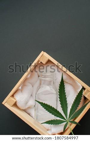 empty glass jar in wooden box with marijuana leaf on dark green background