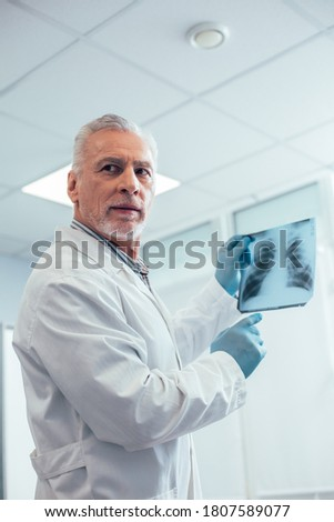 Curious thoughtful male therapist holding a chest x-ray picture and pointing to it while turning