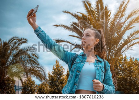 Making picture. Pretty female taking fun self portrait photo. Happy young girl with phone smile, typing texting and taking selfie in summer sunshine urban city. Vanity, social network concept.