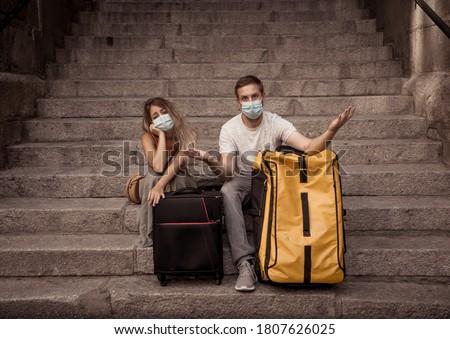 COVID-19 impact in international tourism. Sad tourist couple worried about coronavirus quarantine back home amid new travel regulations. Vacations cancellations due to coronavirus travel restrictions. Royalty-Free Stock Photo #1807626025