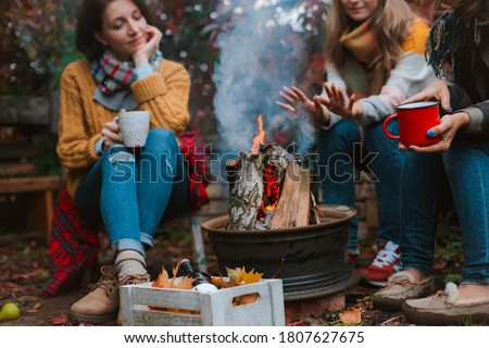 two friends relax comfortably and drink wine on an autumn evening in the open air by the fire in the backyard. The concept of autumn, friendship. top view of the legs #1807627675