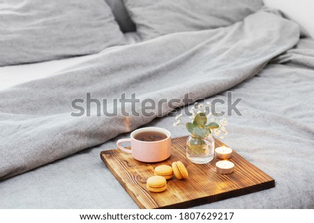 cup of tea with macaroons and candles on wooden tray on bed #1807629217