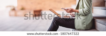 young woman with laptop sitting on the stairs. Person using personal computer outdoors Royalty-Free Stock Photo #1807647322