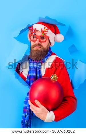 Christmas decorations. Santa looks through paper hole. Santa Claus man holds big christmas ball. Winter holidays. New year. Discount. Sale. Christmas sales. Bearded Santa Claus hold Christmas toy.
