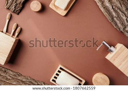 Zero waste, plastic free, sustainable concept. Bamboo bath acessories - soap dish, soap dispenser, tooth brush, organic dry shampoo for personal hygiene on wooden bark texture. Copy space. Top view Royalty-Free Stock Photo #1807662559