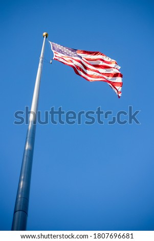 Looking up at a flag on a flagpole with a blue sky Royalty-Free Stock Photo #1807696681