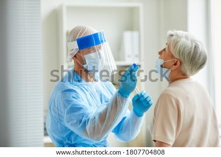 Modern laboratory worker wearing personal protective equipment testing senior woman for coronavirus using nasal swab method Royalty-Free Stock Photo #1807704808