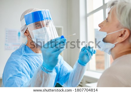 Professional medical worker wearing personal protective equipment testing senior woman for dangerous disease using test stick #1807704814