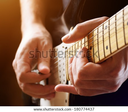Man playing guitar on a stage. Musical concert. Close-up view. #180774437