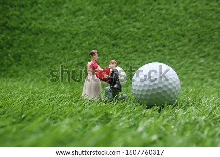 Golf wedding with bride and groom and golf ball on green grass