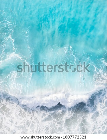 Beautiful aerial view of a wave crashing in a blue ocean during a storm Royalty-Free Stock Photo #1807772521