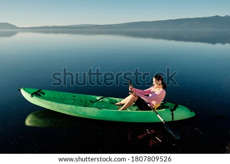 Woman floating in a kayak and using her phone to take pictures and videos of the landscape. Enjoying her freedom. Copy space