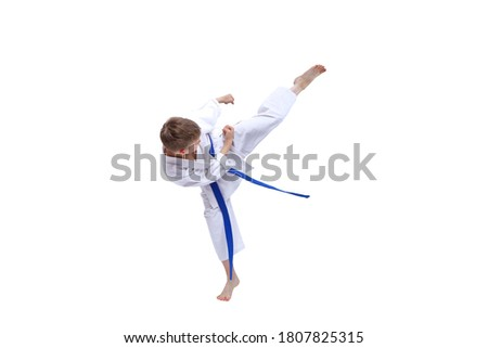 On white isolated background little sportsman with blue belt training kick Royalty-Free Stock Photo #1807825315