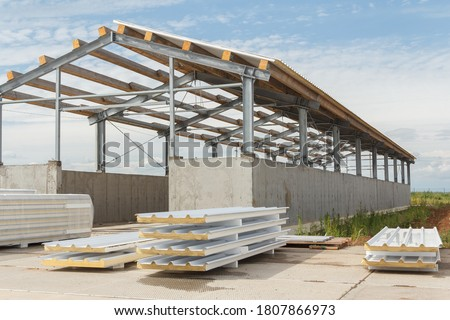 Metal frame of the building with a sandwich panel of insulation on the wall. Construction of a new industrial building. Modern Insulation of the walls of the building panels of insulation. #1807866973