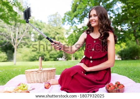 leisure and people concept - happy smiling woman with smartphone on selfie stick and picnic basket sitting on blanket and taking picture at summer park