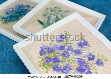 Three embroidered pictures of blue, white and violet flowers - forget-me-nots, lilies of the valley, bluebells flowers - in white frames