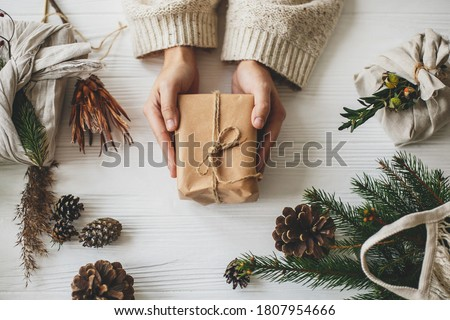 Zero waste Christmas flat lay. Hands holding stylish simple christmas gift in craft paper on rustic white table with fir branches, pine cones. Plastic free sustainable lifestyle Royalty-Free Stock Photo #1807954666