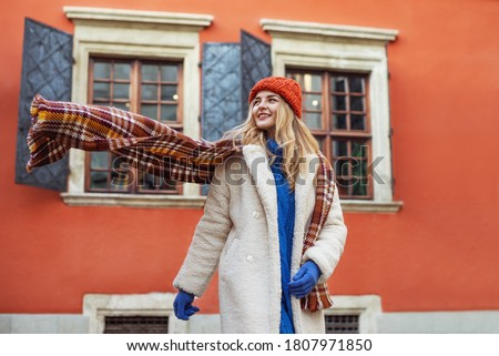 Christmas, winter holidays, lifestyle conception: happy smiling woman wearing white faux fur coat, colorful scarf, hat, walking in street of European city. Copy, empty space for text Royalty-Free Stock Photo #1807971850