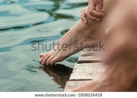 A woman plunges her fingers into the water as she sits on the edge of a wooden deck or jetty, close-up view of her feet #1808036458