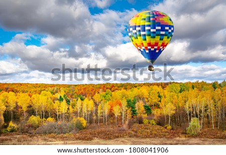 Amazing view of colorful autumn trees with hot air balloon. Concept for fall background. Artistic picture. Beauty world.
