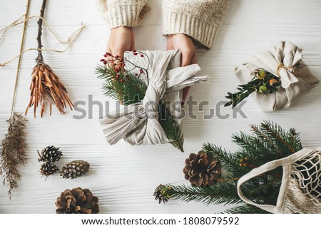 Hands holding stylish christmas gift wrapped in linen fabric with green fir branch and red berries on rustic white table with pine cones, flat lay. Zero waste Christmas, plastic free holidays Royalty-Free Stock Photo #1808079592