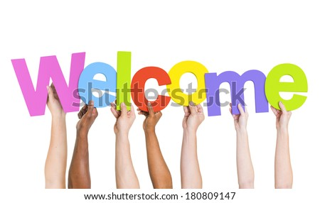 Multi-Ethnic Group Of People Holding The Word Welcome