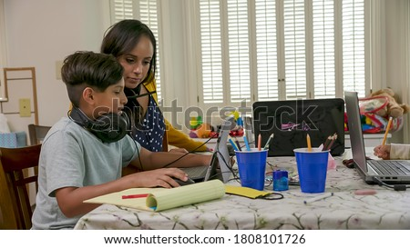 A mom working from home and sharing a small space with her children who are attending school via virtual classrooms stops to help her son. Royalty-Free Stock Photo #1808101726