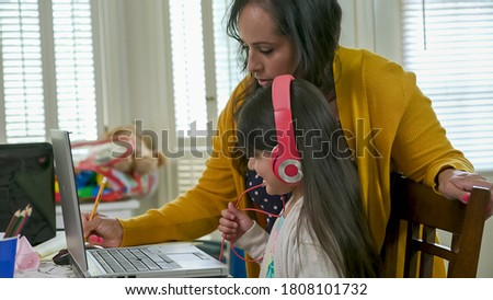 A mom working from home stops and helps her daughter who is attending school via a virtual classroom. Royalty-Free Stock Photo #1808101732