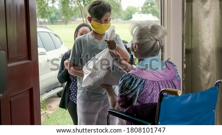 Setting a great example this mother who is part of a volunteer food delivery program takes her children along with her to deliver food to an elderly woman in a wheelchair. Royalty-Free Stock Photo #1808101747