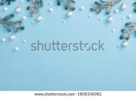 Christmas minimal concept - Christmas composition with snowy fir branch and white bauble. Horizontal top composition, flat lay, view from above. Pastel blue background with copy space #1808106082