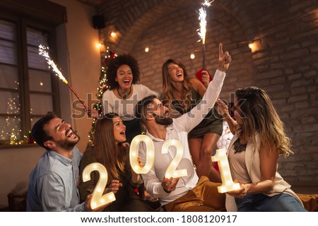 Group of young friends having fun at New Years party, holding illuminative numbers 2021 representing the upcoming New Year and waving with sparklers at midnight countdown #1808120917