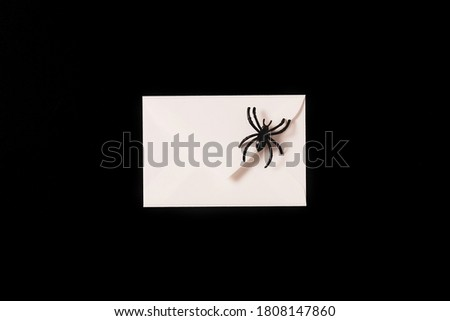 Cartoon Halloween background white envelope with black spider on black backdrop. Copy space. Flat lay style. Halloween abstract background. Dark retro black and white background.