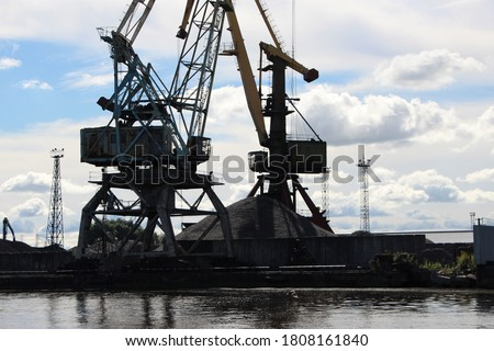 Silhouettes of the lower part of the port cranes against the blue sky (cabin; slewing support device; portal; carts; counterweight) and mountains of bulk materials for loading #1808161840