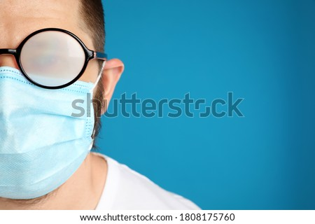 Man with foggy glasses caused by wearing disposable mask on blue background, space for text. Protective measure during coronavirus pandemic Royalty-Free Stock Photo #1808175760