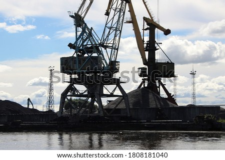 Silhouettes of the lower part of the port cranes against the blue sky (cabin; slewing support device; portal; carts; counterweight) and mountains of bulk materials for loading #1808181040