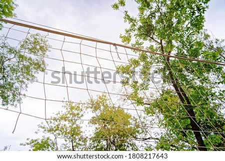 The volleyball net is on the background of the sky with clouds. The net is stretched between the trees in the yard. Concept for street sports, outdoor games and competitions. #1808217643