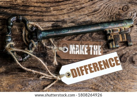 an old rusty key on a ribbed wooden table and labels with the text make the difference