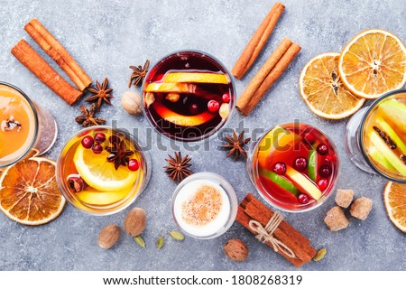 Various autumn or winter seasonal alcohol hot cocktails - mulled wine, glogg, grog, eggnog, warm ginger ale, hot buttered rum, punch, mulled apple cider on gray background, top view with copy space #1808268319
