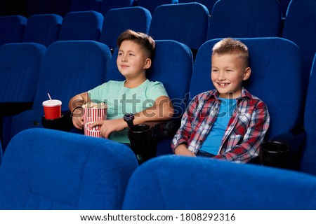 Side view of two smiling boys watching comical movie together in empty cinema. Male friends holding popcorn and sweet water. Children laughing and having rest on weekend. Concept of childhood.