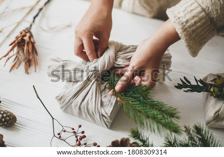 Florist preparing zero waste Christmas gift. Plastic free holidays. Hands decorating stylish christmas gift in linen fabric with green fir branch on white rustic table with pine cones and berries. Royalty-Free Stock Photo #1808309314