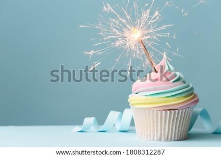 Pastel rainbow birthday cupcake with sparkler Royalty-Free Stock Photo #1808312287