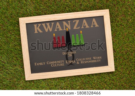 Kwanzaa Ujima (African for Collective Work & Responsibility ) Kinara (Candle Holder) Blackboard on green turf grass