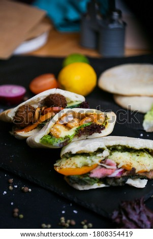 Greek gyros pita wrapped sandwich with meat slices and vegetables #1808354419