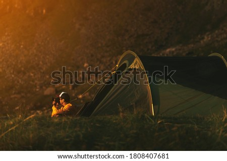 Camping with tent in Lofoten islands, Northern Norway, Kvalvika beach Person sitting in front of tent and taking pictures of beautiful sunset.