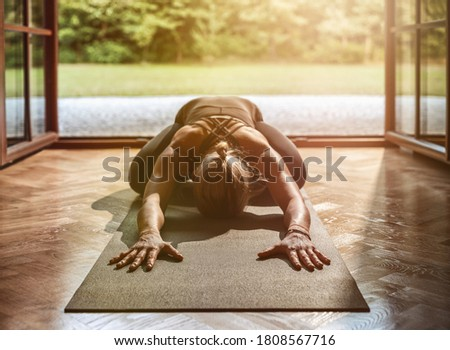 Young woman practicing yoga at home Royalty-Free Stock Photo #1808567716