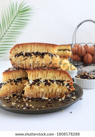 Martabak Manis is Indonesia dessert. Sweet Martabak with chocolate, cheese, peanut. this picture in white background and blurry, selective object.