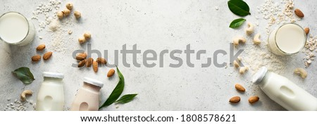 Vegan plant based milk and ingredients, top view, copy space. Various dairy free, lactose free nut and grains milk, substitute drink, healthy eating. Royalty-Free Stock Photo #1808578621