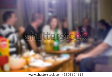 People sitting at restaurant or bar, drinking and having a conversation. Birthday party or a nightout. Blurred image for background use.