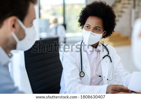 Black female doctor communicating with a patient while wearing protective face mask during medical appointment.  Royalty-Free Stock Photo #1808630407